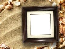 Картинная рамка на раковинах и предпосылке песка Стоковые Изображения RF