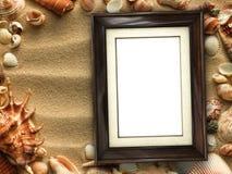 Картинная рамка на раковинах и предпосылке песка Стоковые Изображения
