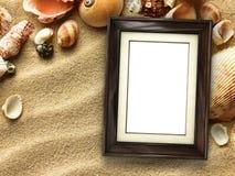 Картинная рамка на раковинах и предпосылке песка Стоковая Фотография