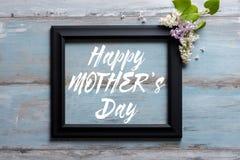 Картинная рамка с цветками сирени и счастливое сообщение дня ` s матери на деревянной предпосылке Стоковые Фотографии RF