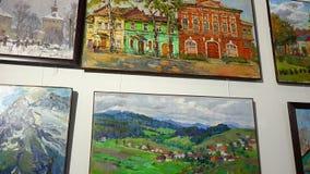 Картины местными художниками покрасили вид масла на стене выставочного зала иллюстрация штока