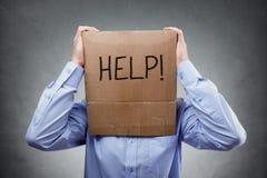 Картонная коробка на голове бизнесмена попросить помощь стоковые изображения rf