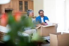 Картонная коробка старших пар unpackaging в живущей комнате Стоковые Фотографии RF