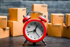 Картонные коробки и красный будильник Срок доставки Ограниченная поставка, недостаток товаров в лихорадке запаса, навязчивой рекл стоковые изображения rf
