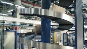 Картонные коробки на конвейерной ленте в фабрике зажим Производственная линия на которую коробки двигают в спираль сток-видео
