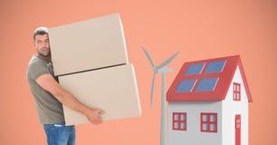 Картонные коробки нося работника доставляющего покупки на дом ветрянкой и домом Стоковая Фотография