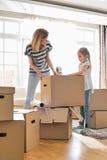 Картонные коробки упаковки матери и дочери дома Стоковая Фотография