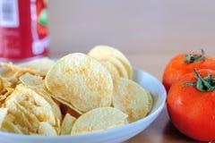 Картофельные стружки и томат Стоковая Фотография