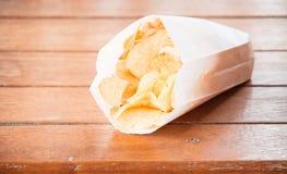 Картофельные стружки в бумажной сумке на таблице Стоковое фото RF