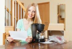 Карточка гарантии чтения женщины для новой машины дома int кофе стоковые фотографии rf