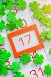 Карточка дня ` s St. Patrick праздничная Зеленые quatrefoils на календаре с апельсином обрамили 17-ое марта Стоковая Фотография