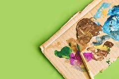 Карточка картона при мазки краски используемые как палитра для красить и paintbrush на светлом свежем зеленом стиле весны стоковое изображение