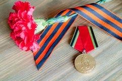 Карточка 9-ое мая - медаль юбилея Великой Отечественной войны с красными гвоздикой и лентой St. George Стоковая Фотография RF