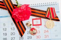 Карточка 9-ое мая праздничная - медали юбилея Великой Отечественной войны с красными гвоздиками и лентой St. George Стоковые Фото