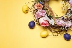 карточка пасха Покрашенные пасхальные яйца в гнезде на желтой предпосылке Стоковые Изображения RF