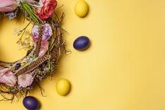карточка пасха Покрашенные пасхальные яйца в гнезде на желтой предпосылке Стоковое Изображение