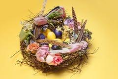 карточка пасха Покрашенные пасхальные яйца в гнезде на желтой предпосылке Стоковая Фотография