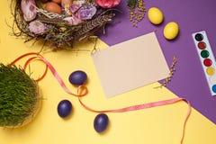карточка пасха Покрашенные пасхальные яйца в гнезде на желтой предпосылке Стоковые Изображения