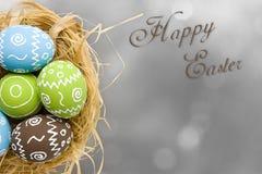 карточка пасха Покрашенные пасхальные яйца в гнезде на серой предпосылке стоковое изображение