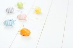 карточка пасха Разбросанные пастельные пасхальные яйца на деревянной предпосылке Стоковое фото RF