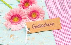 Карточка подарка с немецким словом, Gutschein, ваучером середин или талоном и красивыми розовыми цветками Стоковое Изображение RF
