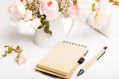 Карточка праздника, красивый свежий розовый английский язык подняла, подарок, тетрадь, ручка, карандаш на белой предпосылке День  Стоковая Фотография