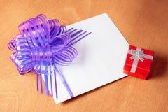 Карточка примечания с фиолетовым смычком и красной подарочной коробкой Стоковая Фотография