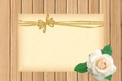 Карточка украшенная с золотыми смычком и белой розой на деревянном Стоковые Фото