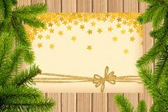 Карточка украшенная с золотыми смычком и звездами на деревянной предпосылке Стоковая Фотография
