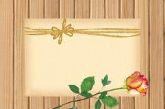 Карточка украшенная с золотым смычком и красивая подняла на деревянное Стоковое Изображение RF