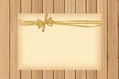 Карточка украшенная с золотым смычком на деревянном Стоковое Фото