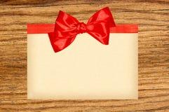 Карточка украшенная с красными лентой и смычком на деревянном Стоковое Изображение