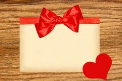 Карточка украшенная с красными лентой, смычком и сердцем на деревянном Стоковая Фотография