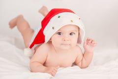 Карточка Xmas с милым ребёнком с шляпой santa на бежевой воздушной предпосылке briht с космосом экземпляра стоковое фото