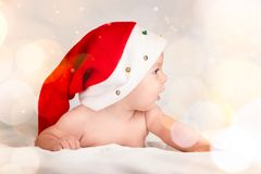 Карточка Xmas с милым ребёнком с шляпой santa на бежевой воздушной предпосылке briht с космосом экземпляра стоковое изображение
