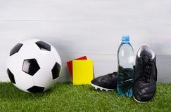 Карточки ботинок, футбольного мяча, бутылки с водой и штрафа для судьи, стойки на траве, на серой предпосылке для стенда Стоковая Фотография RF