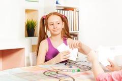 Карточки девушки играя сидя на таблице игры Стоковое Фото