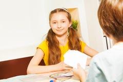 Карточки девушки играя сидя против ее оппонента Стоковая Фотография RF