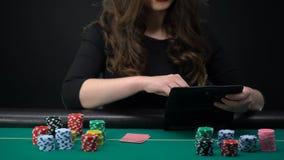 Карточки женского игрока казино проверяя и повышение, женщина принимая риск в игре в покер акции видеоматериалы