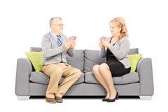 Карточки зрелых пар играя и сидеть на софе Стоковые Фотографии RF
