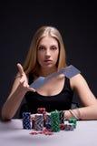 Карточки молодой женщины бросая играя в казино Стоковые Фотографии RF