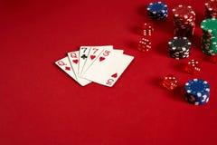 Карточки покера и играя в азартные игры обломоки на красной предпосылке Стоковые Фотографии RF