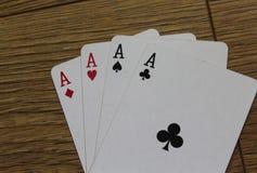 Карточки покера на деревянном backround, комплекте туза клубов, диамантах, лопатах, и сердцах стоковые изображения