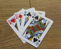 Карточки покера на деревянном backround, комплекте ферзей клубов, диамантах, лопатах, и сердцах стоковое изображение rf