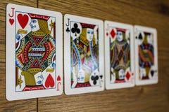 Карточки покера на деревянном backround, комплекте jacks клубов, диамантах, лопатах, и сердцах стоковое фото