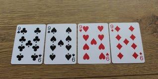 Карточки покера на деревянном backround, комплекте nines клубов, диамантах, лопатах, и сердцах стоковые фото