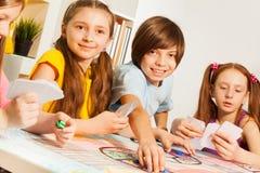 4 карточки друзей играя сидя на таблице игры Стоковое Фото