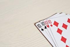4 10 карточки рук покера играя на светлой предпосылке стола Стоковое Изображение