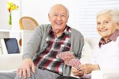 Карточки старших пар играя дома стоковая фотография
