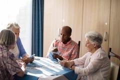 Карточки старших людей играя на таблице Стоковое Изображение
